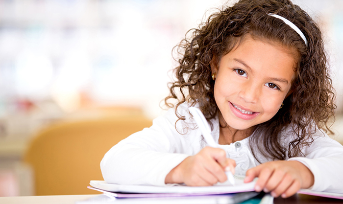 Cute little girl studying at the library and smiling; Shutterstock ID 119721871; PO: aol; Job: production; Client: drone